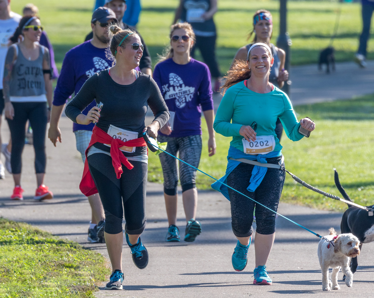A group of women and two dogs run in a 5K