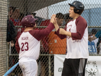 Two male Special Olympics Minnesota softball athletes give each other high fives
