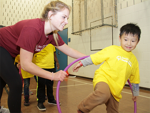 A female volunteer helps a male Special Olympics Minnesota Young Athlete through a hula hoop
