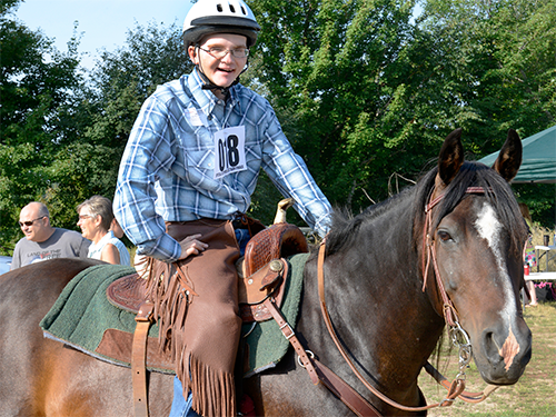 A Special Olympics Minnesota equestrian athlete smiles from atop his brown horse