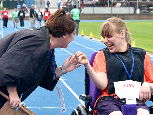 A Special Olympics Minnesota athlete in a wheelchair talks to an event volunteer
