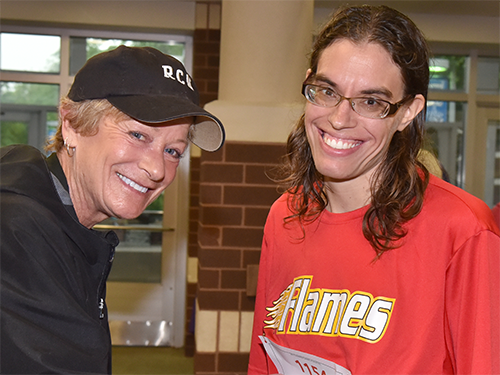 A Special Olympics Minnesota coach and athlete smile at the camera