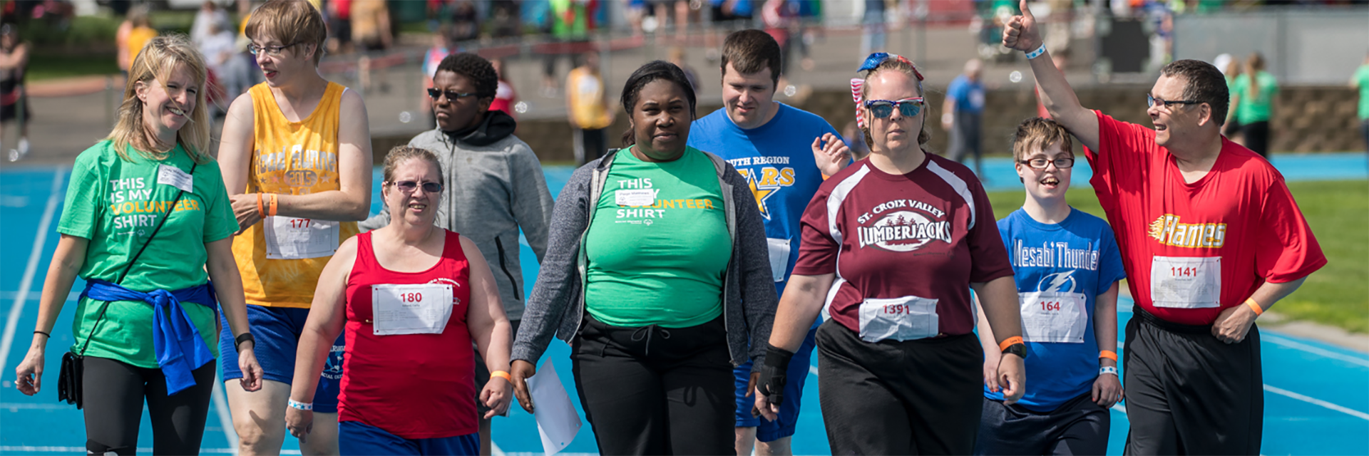 A group of Special Olympics Minnesota athletes and volunteers walk across a track