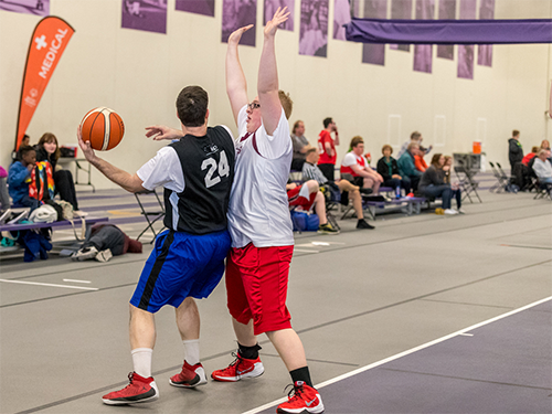 Two Special Olympics Minnesota basketball players face off on the court
