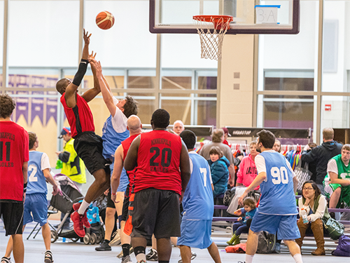 A player from a Special Olympics Minnesota basketball team jumps to shoot a basket