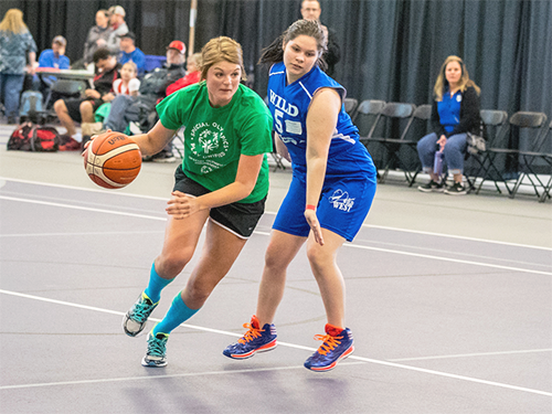 Two Special Olympics Minnesota Unified basketball players run down the court