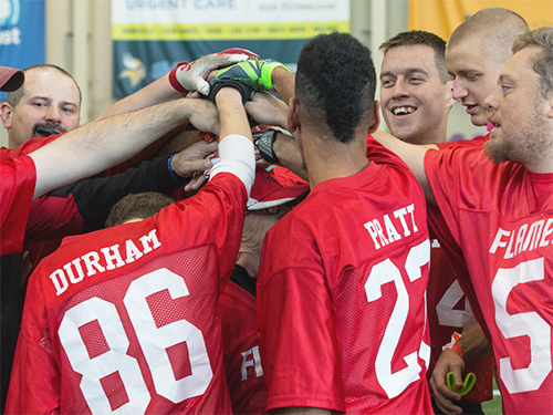 A Special Olympics Minnesota Unified flag football team joins hands in a huddle