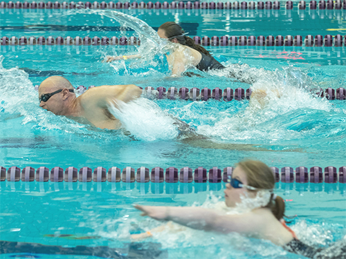 Three Special Olympics Minnesota swimmers compete in a pool