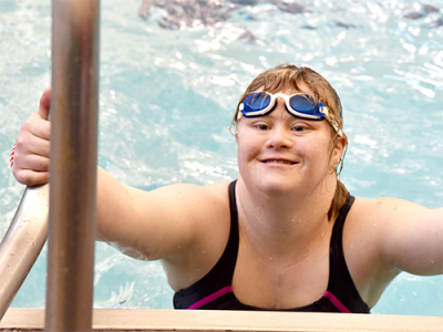 A Special Olympics Minnesota swimmer climbs out of the pool