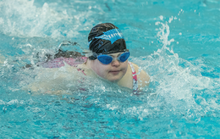 A Special Olympics Minnesota athlete wearing goggles and a swim hat swims