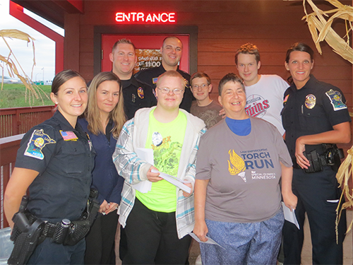 Special Olympics Minnesota staff, law enforcement officers and Famous Dave's staff pose for a Tip-A-Cop photo