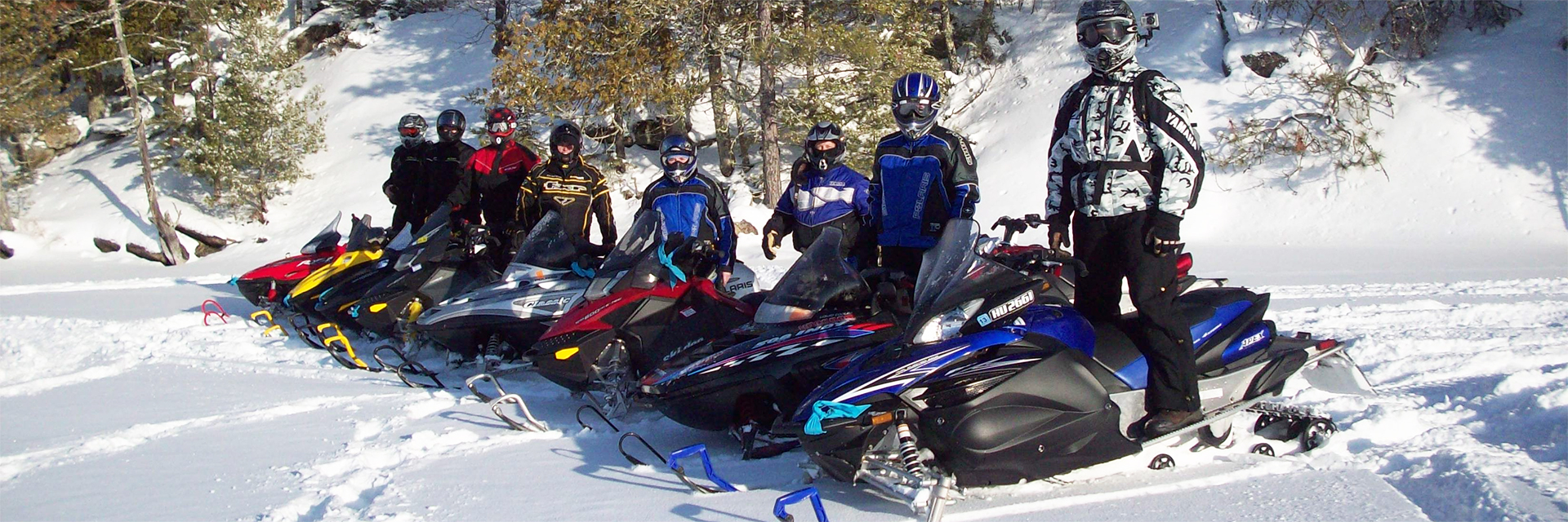Eight snowmobiles and riders stand in a row in the snow