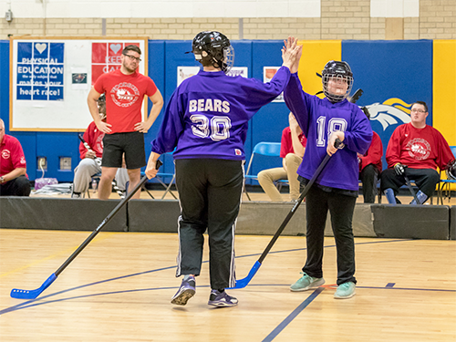 Two Special Olympics Minnesota athletes in poly hockey gear and purple jerseys give each other high 5s