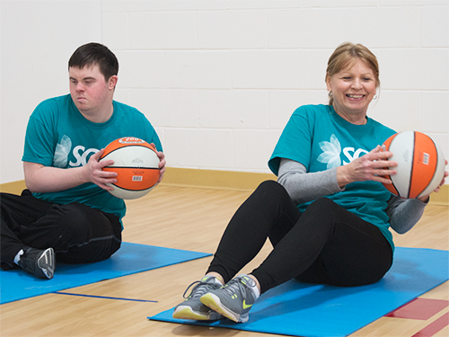 Two Special Olympics Minnesota SOfit participants exercising with basketballs