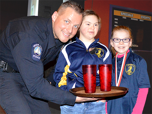 A police officer poses with two Special Olympics Minnesota athletes at a Tip-A-Cop event for the Law Enforcement Torch Run