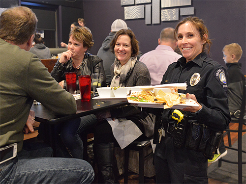 A police officer poses with a diner at a Tip-A-Cop event for the Law Enforcement Torch Run