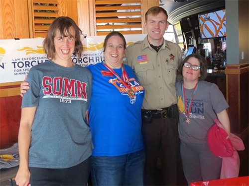 A police officer poses with three Special Olympics Minnesota athletes at a Red Robin Tip-A-Cop event for the Law Enforcement Torch Run