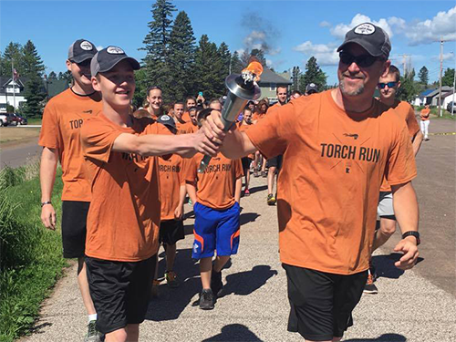 Two men wearing orange Special Olympics Minnesota Law Enforcement Torch Run shirts pass the Flame of Hope between them
