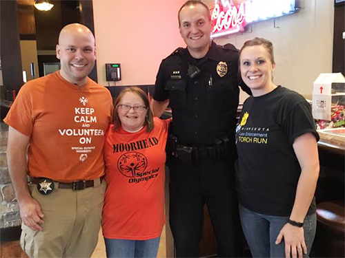 A group of Special Olympics Minnesota athletes, volunteers and law enforcement officers pose at a Tip-A-Cop location in Moorhead Minnesota