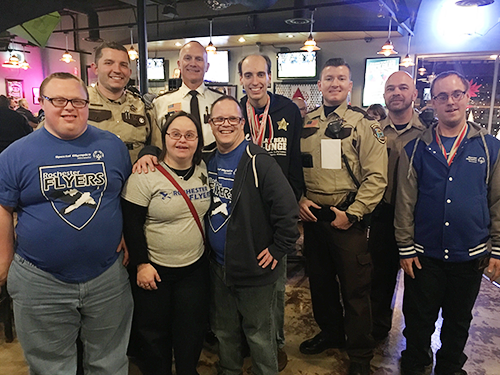 A group of Special Olympics Minnesota athletes and law enforcement officers pose at a Tip-A-Cop location in Rochester Minnesota