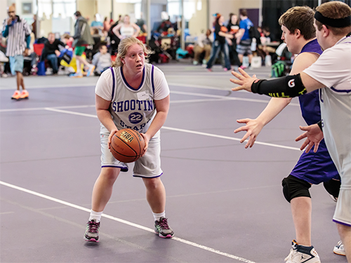 A Special Olympics Minnesota athlete holding a basketball faces players from the opposite team