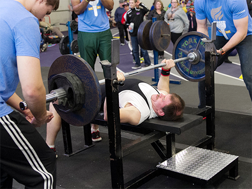 A Special Olympics Minnesota powerlifting athlete bench presses weights