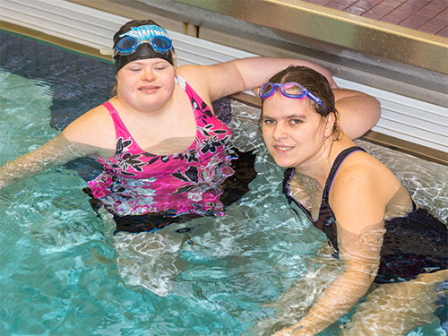 Two Special Olympics Minnesota swimming athletes smile at the camera