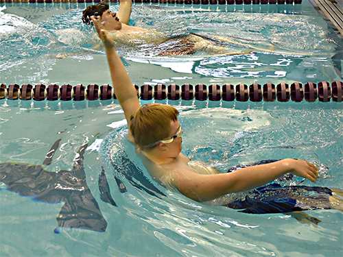 A Special Olympics Minnesota swimming athlete does the backstroke