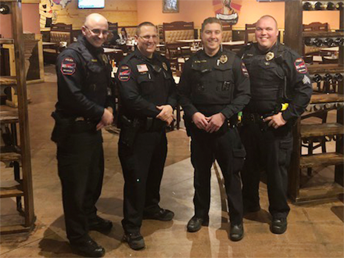 Four law enforcement officers pose during a Special Olympics Minnesota Tip-A-Cop event