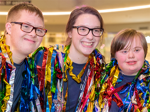 Three Unified Dance Marathon participants wear shiny ribbons and smile at the camera