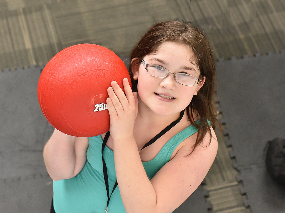 A Special Olympics Minnesota athlete holds a ball and looks up at the camera
