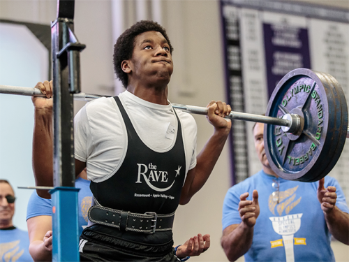 A Special Olympics Minnesota athlete prepares for a squat during a powerlifting competition