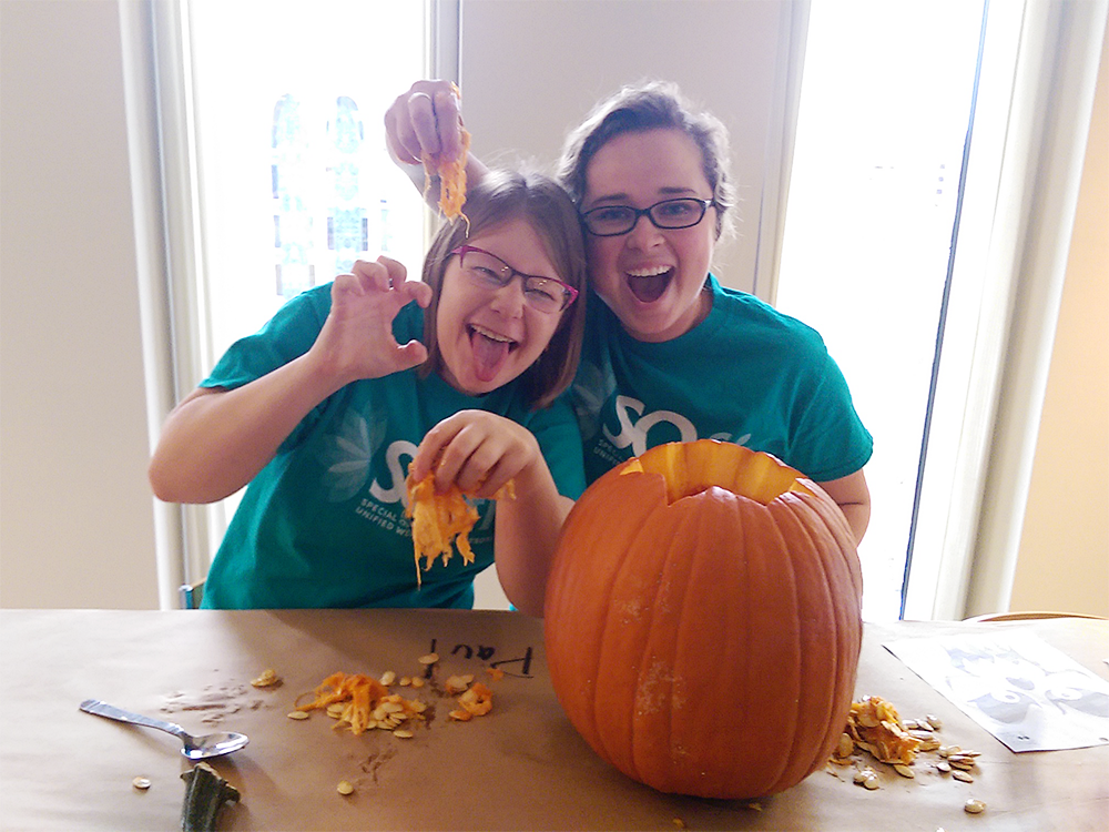 A Special Olympics Minnesota athlete and Unified Partner make faces at the camera while carving pumpkins