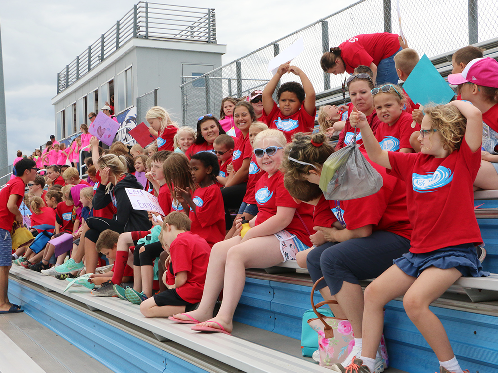 A group of people wearing red shirts cheers from the bleachers at Special Olympics Minnesota Summer Games