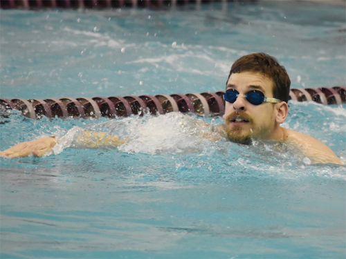 A Special Olympics Minnesota athlete wearing goggles swims in a pool