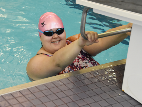 A Special Olympics Minnesota swimming athlete wearing goggles smiles at the camera