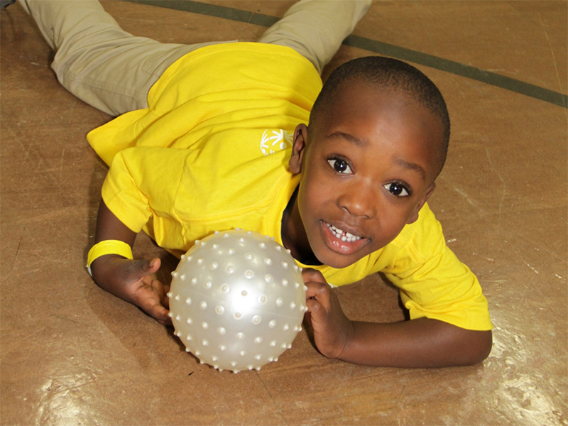 A Special Olympics Minnesota Young Athlete holds a ball while looking at the camera