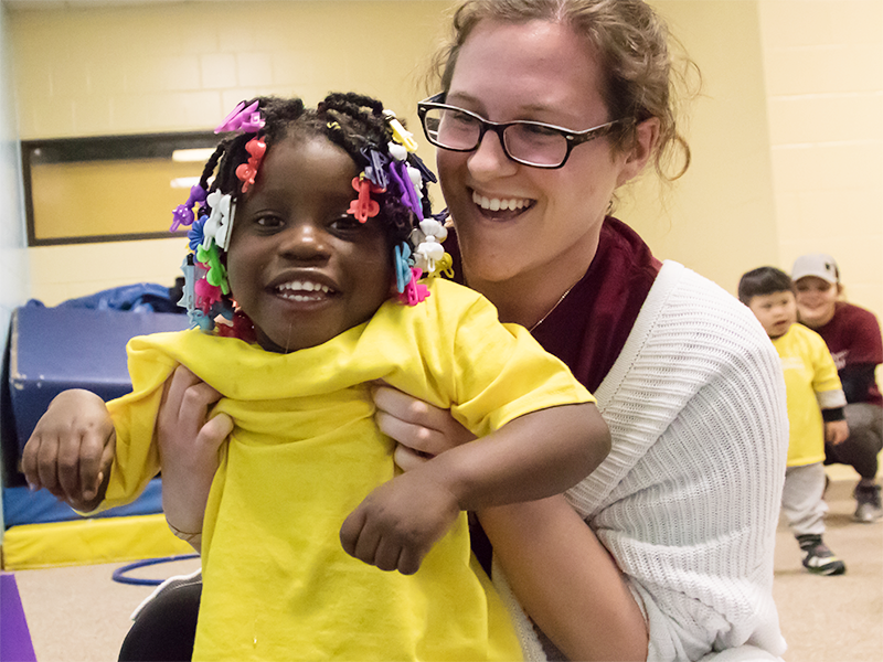 A smiling Special Olympics Minnesota volunteer holds a smiling Young Athlete