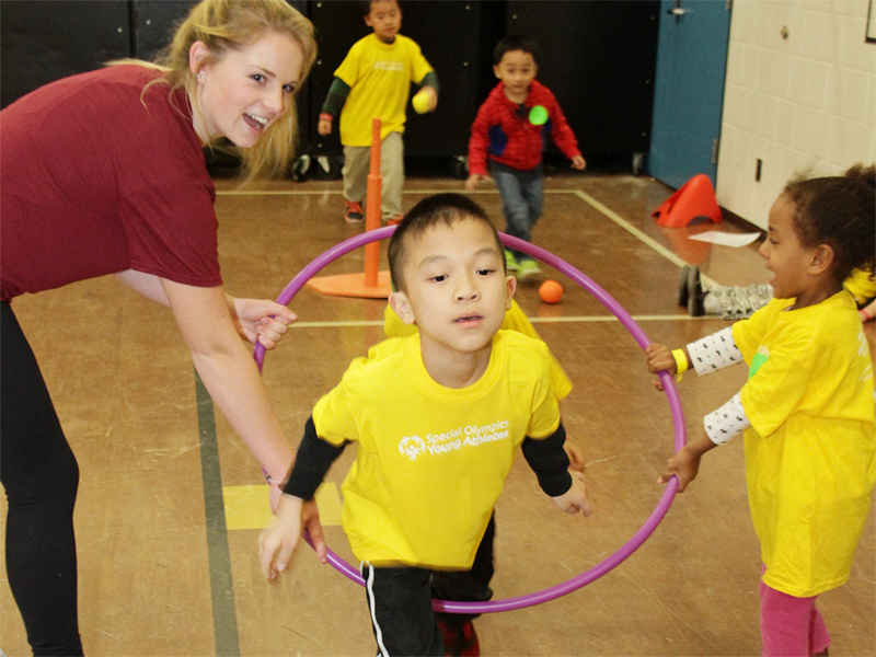 Special Olympics Minnesota Young Athletes play with hula hoops and balls with the help of a volunteer