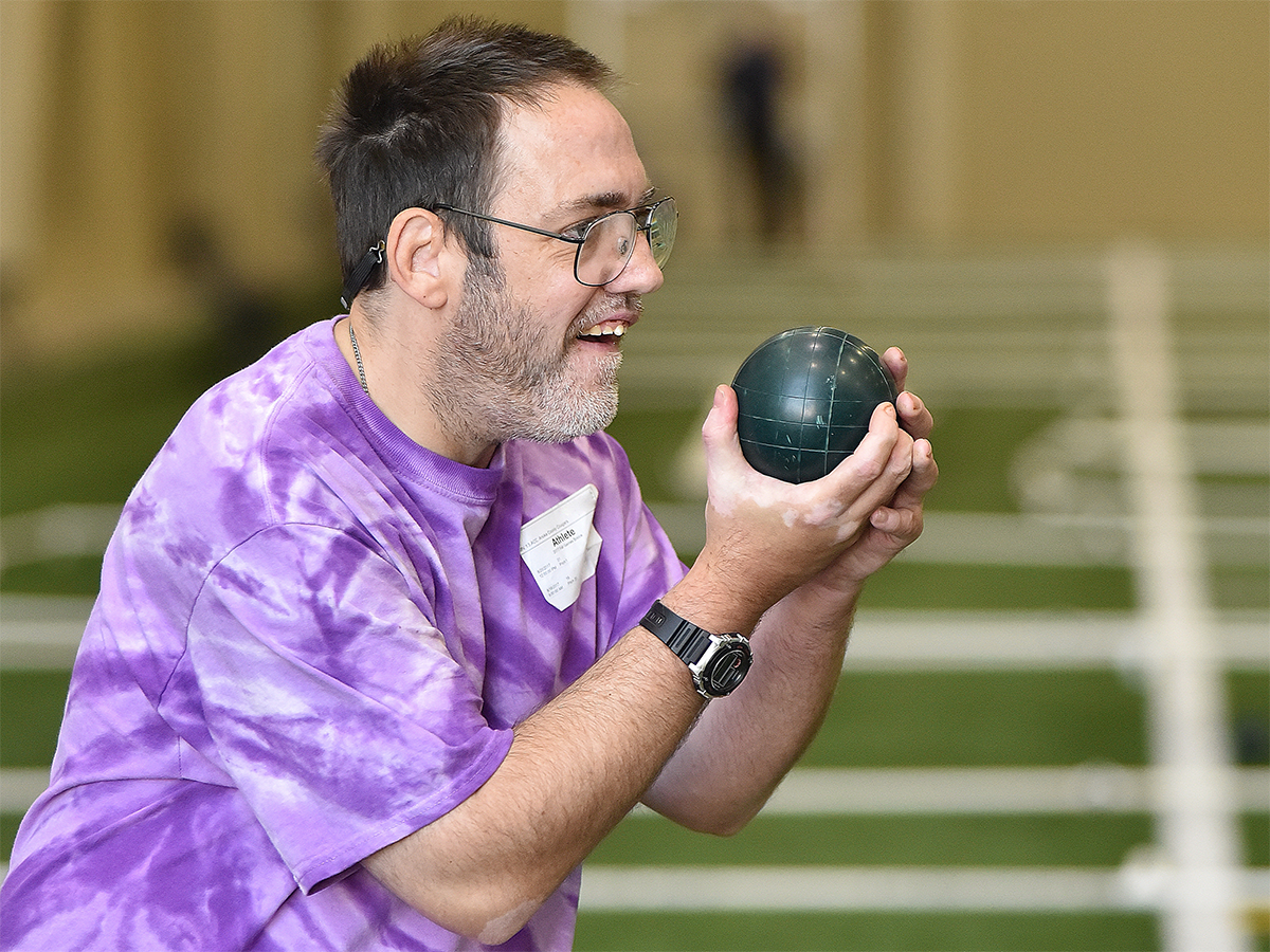 A Special Olympics Minnesota athlete lifts a bocce ball
