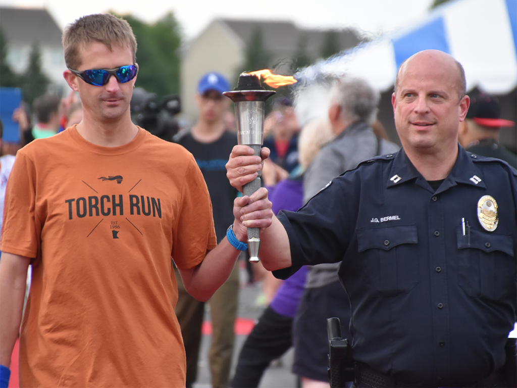 Special Olympics athlete Dave Larson and law enforcement officer carry the Flame of Hope at 2017 Summer Games