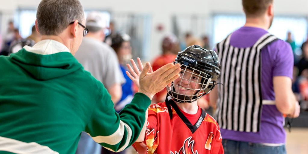 A coach gives his player a high five during a floor hockey game