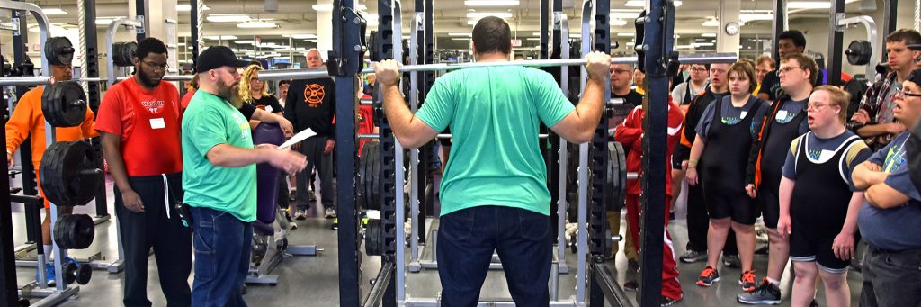 Athletes cheer on a competitor in the squat rack