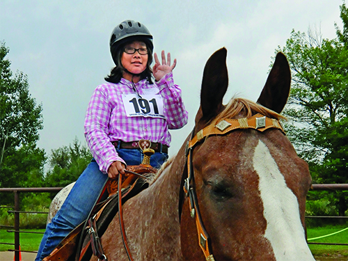 A Special Olympics Minnesota equestrian athlete waves from the top of a horse