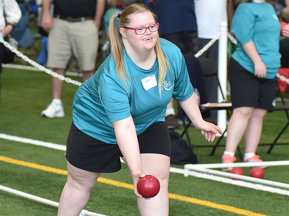 A Special Olympics Minnesota athlete begins to roll a bocce ball