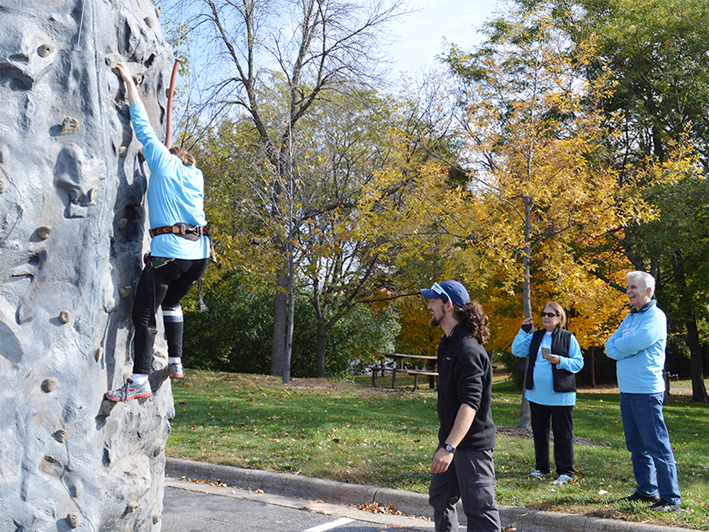 A Special Olympics Minnesota athlete scales a rock wall at a SOfit rally while others watch