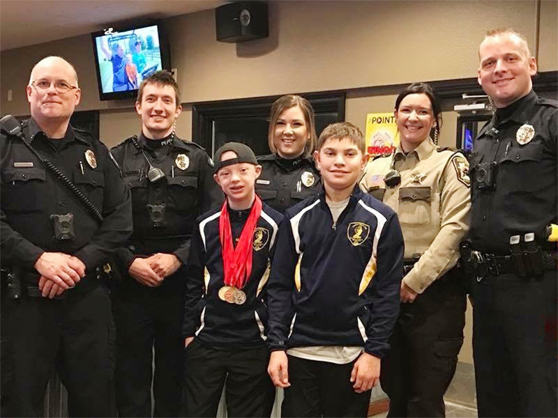 Two Special Olympics Minnesota athletes pose with law enforcement officers from the Scott County Sheriff's Office