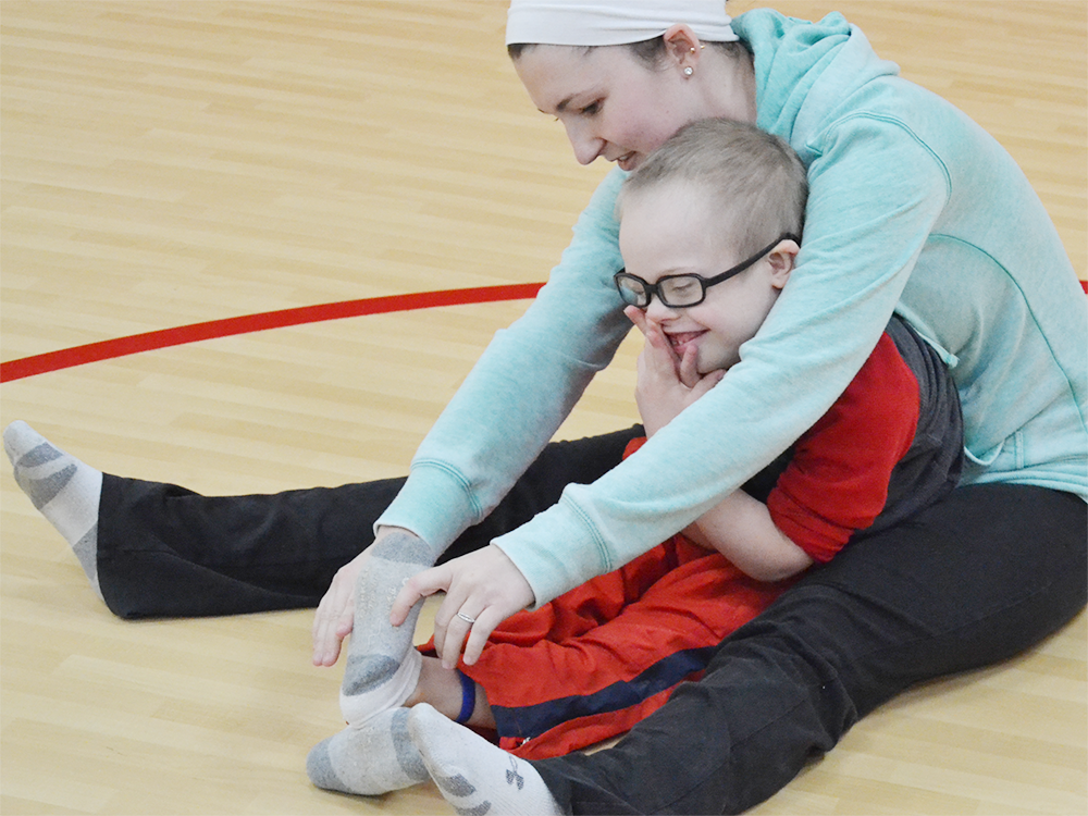 A Special Olympics Minnesota Young Athlete sits with a volunteer and laughs while she touches his toes