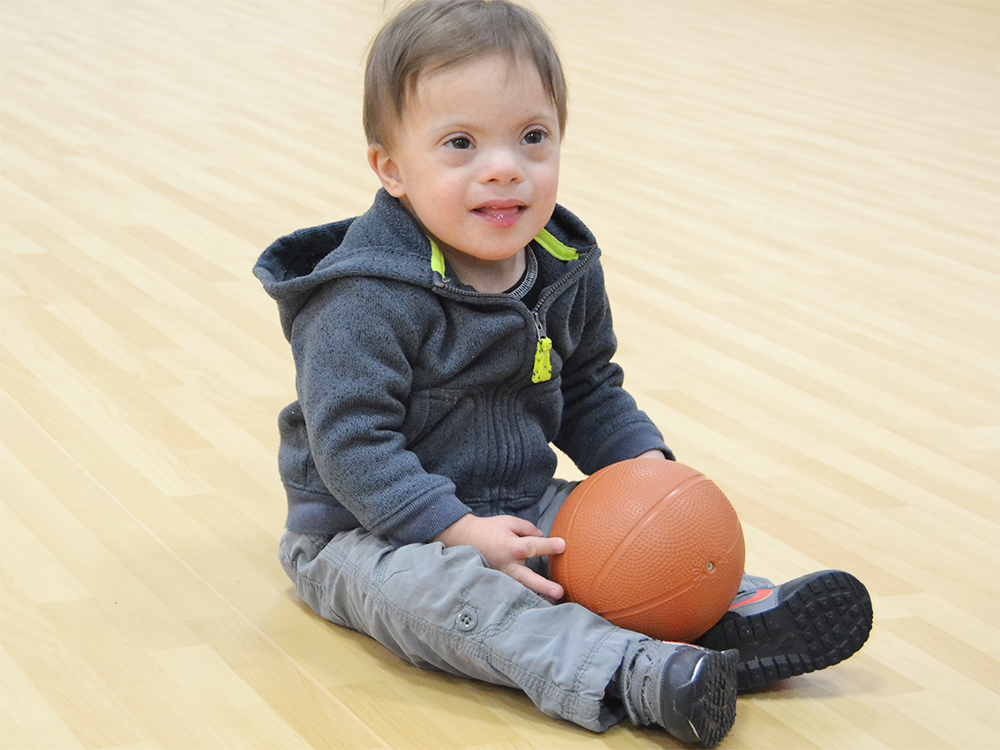 A Special Olympics Minnesota Young Athlete sits holding a small basketball