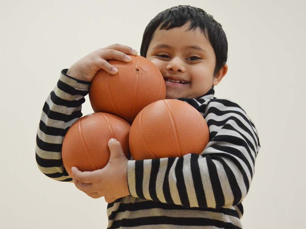 A smiling Special Olympics Minnesota Young Athlete holds three small basketballs piled up in his arms